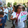 """Roshawnda Brooks holds a sign that says, """"Cage Free Kids!"""" as she participates in Lights for Liberty, on Friday, July 12, 2019, to protest the conditions at migrant detention centers across the country. In Kokomo, participants held candles as they walked from Sol House to the Howard County Courthouse.<br /> Kelly Lafferty Gerber 