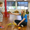 Zara Hooper, right, holds up a dinosaur toy and makes 4-year-old Cruz Dean laugh as she works at Kokomo YMCA's Play & Learn Center on May 8. In addition to her job at the YMCA, Zara also works at Heritage Lanes and is a full-time student. After she graduates high school she will be attending IUK and pursuing elementary education.<br /> Kelly Lafferty Gerber | Kokomo Tribune