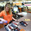 Zara Hooper sprays shoes before filing them away at Heritage Lanes bowling alley on May 4, one of her two jobs in addition to being a full-time student.<br /> Kelly Lafferty Gerber | Kokomo Tribune