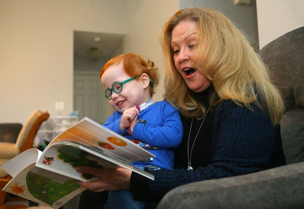 Marcus giggles as his mom Kelly Lively reads a book to him at home on Feb. 16, 2019. Nurses and doctors who thought Marcus would never make it past the hospital after he was born with serious health conditions, has thrived since Kelly began fostering and eventually adopting him. Kelly felt called to adopt Marcus after seeing a photo of him.<br /> Kelly Lafferty Gerber | Kokomo Tribune