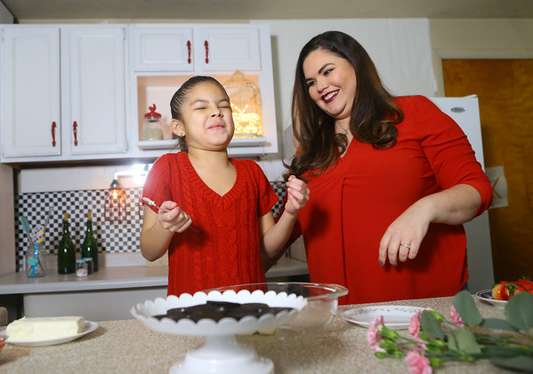 """Grethel's daughter, 8-year-old Julia, laughs as she assists her mom and prepares a Valentine's treat on Jan. 25 for """"Azucar y pimienta,"""" Grethel's cooking show in Nicaragua. Julia is a regular contributor to Grethel's show, showing kids that they can cook too. Julia's favorite part about helping her mom is eating the food afterward.<br /> Kelly Lafferty Gerber 
