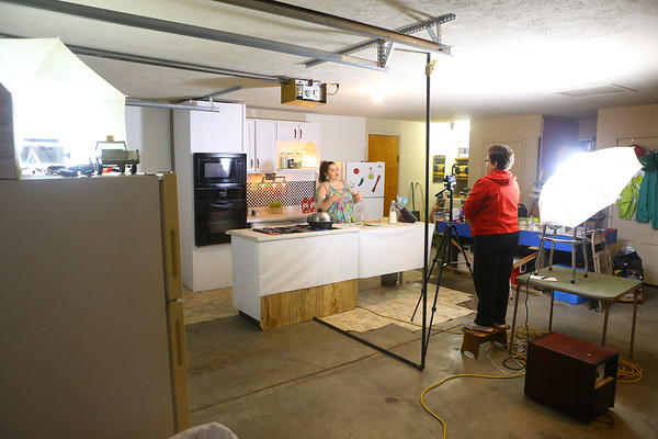 """Studio lights are set up and pointed toward Grethel as she films """"Azucar y pimienta,"""" a Nicaraguan cooking show, from her Greentown garage. Grethel's mom Carmen Pasos, who was visiting Grethel on Jan. 2, stands behind the camera to help film.<br /> Kelly Lafferty Gerber 