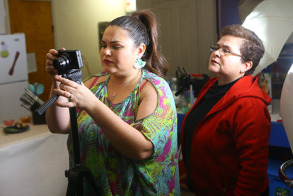 """Grethel Mendoza Pasos Keeney looks over footage on the back of her camera as her mom Carmen Pasos looks over her shoulder. Carmen helped film """"Azucar y pimienta"""" while she was visiting Grethel in Greentown in January.<br /> Kelly Lafferty Gerber   Kokomo Tribune"""