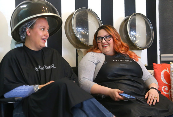 Rebeckah Reichert, right, chats with her client Sharon Breitenbach as she sits under the dryer at Terrie and Co. Salon in Peru. Reichert, who was recently hired as a hairstylist by the Peru salon, is 80 percent deaf and fluent in American Sign Language.<br /> Kelly Lafferty Gerber | Kokomo Tribune