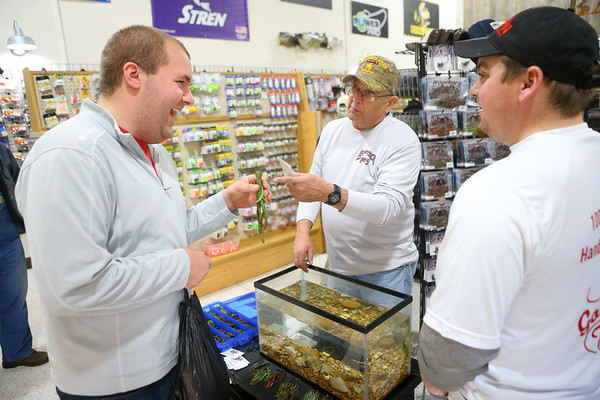 Thomas Gish, left, talks lures with Alan Miller from Ledgerock Lures and Nate Bontrager, right, from B&N Custom Baits during SoreMouth Tackle's grand opening at 1500 N. Reed Road inside the Kokomo Event Center on Saturday, March 30, 2019.<br /> Kelly Lafferty Gerber   Kokomo Tribune
