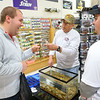 Thomas Gish, left, talks lures with Alan Miller from Ledgerock Lures and Nate Bontrager, right, from B&N Custom Baits during SoreMouth Tackle's grand opening at 1500 N. Reed Road inside the Kokomo Event Center on Saturday, March 30, 2019.<br /> Kelly Lafferty Gerber | Kokomo Tribune