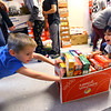 Western Primary 2nd graders load collected cans and dry goods into boxes and move them to the back door of the school on Nov. 25, 2019. The kindergarten, first and second graders collected the 8000 plus food items during a contest at the school to be donated to the Rescue Mission. Zane Stafford and Aarau Shukla push a box of dry goods through the hall.<br /> Tim Bath   Kokomo Tribune
