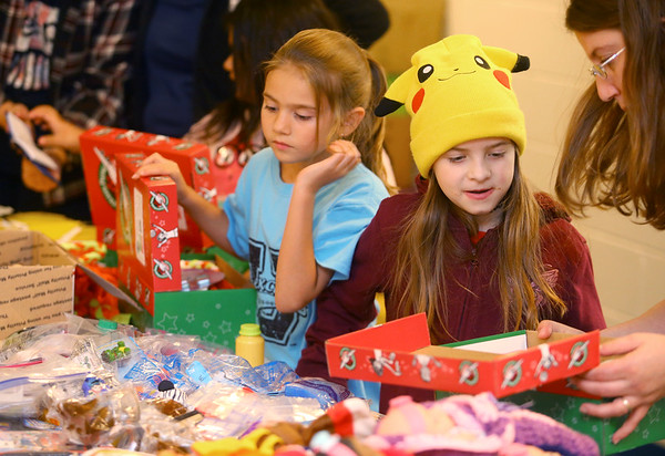 Aaliyah Power, 7, right, and Arianna DeWald, 7, left, pick out toys to put in shoeboxes during a shoebox packing party for Operation Christmas Child at Brookside Free Methodist Church on November 13, 2019.<br /> Kelly Lafferty Gerber   Kokomo Tribune