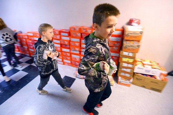 Western Primary 2nd graders load collected cans and dry goods into boxes and move them to the back door of the school on Nov. 25, 2019. The kindergarten, first and second graders collected the 8000 plus food items during a contest at the school to be donated to the Rescue Mission.<br /> Tim Bath   Kokomo Tribune