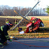 A single vehicle accident injured one person and took down power lines on 350 North between 200 and 300 West on Monday morning Nov. 25, 2019. The red Chevy Cobalt wrapped around a utility pole just behind the driver, trapping him inside. He was awake and talking with firefighers complaining of pain in the shoulder. Until power was cut from the high voltage power lines that surrounded the car, rescuers were unable to cut him out. Power was cut after about 30 minutes with about 15 minutes to cut him out before he was transported by air helicopter to St. Vincent in Indianapolis. Galveston Volunteer firefighters prepare to cut him out as soon a power is shut off.<br /> Tim Bath   Kokomo Tribune