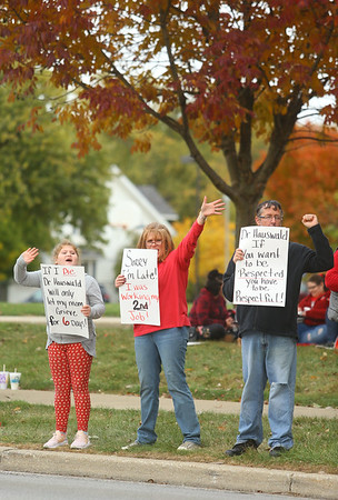 From left: 9-year-old Kendall Novinger, a third grader at Sycamore Elementary, her mom Stephanie Novinger, a special education teacher at Sycamore Elementary, and Michael Kitts, a substitute teacher, hold signs and wave to passing cars on South Washington Street as they rally alongside Kokomo Teachers Association members and supporters outside of the Kokomo School Corporation Administrative Services Center during the second round of contract negotiations on Thursday, October 24, 2019.<br /> Kelly Lafferty Gerber | Kokomo Tribune