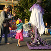 5-year-old Lilly Davis, dressed like Sky from Paw Patrol, reaches in for a piece of candy as she glances up at Northwestern's Cybertooth 3940's ghost robot as she and her mom Elizabeth Davis explore downtown Kokomo during First Friday, Oct. 4, 2019.<br /> Kelly Lafferty Gerber | Kokomo Tribune