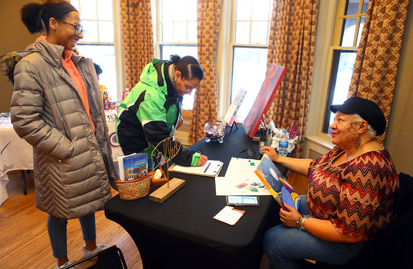 Ramona Daniels, right, owner of Artyside Studio talks with 14-year-old Rylee Morris, left, and her mom Kimberly Morris during the Black History Month African-American Artisan Fair at the Elliott House on Thursday, Feb. 27, 2020.<br /> Kelly Lafferty Gerber | Kokomo Tribune
