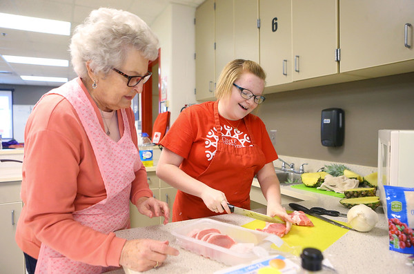 Shirley Watson, left, watches as 14-year-old Harlee Reel cuts chicken after teaching her how to do it as their team prepares a dish for the judges during the Chopped competition on Tuesday, Feb. 18, 2020, where Western Middle School FACS club students and Waterford Place residents teamed up to prepare and cook a dish using certain ingredients in 45 minutes.<br /> Kelly Lafferty Gerber | Kokomo Tribune