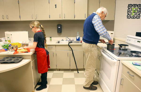 12-year-old Emma Williams, left, and Jim Thrasher, right, prepare a dish for their team during the Chopped competition on Tuesday, Feb. 18, 2020, where Western Middle School FACS club students and Waterford Place residents teamed up to prepare and cook a dish using certain ingredients in 45 minutes.<br /> Kelly Lafferty Gerber | Kokomo Tribune