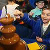 Ace Powless, 6, dips his marshmallow into the chocolate fountain set up at Trilogy Health Services table during the 18th annual Chocolate Celebration, benefiting the Samaritan Caregivers, at Kokomo's First Church of the Nazarene on Friday, Feb. 7, 2020.<br /> Kelly Lafferty Gerber | Kokomo Tribune