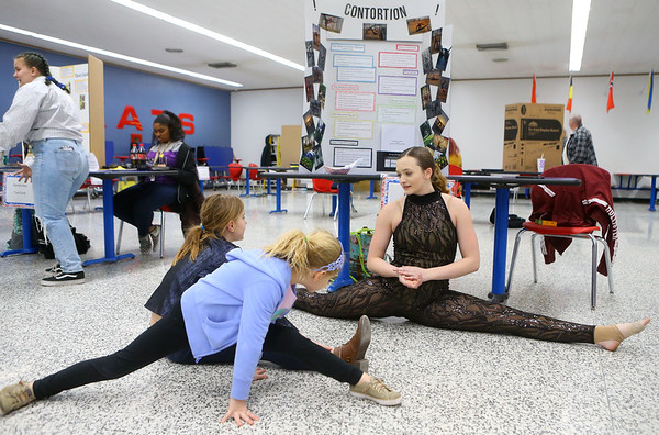 "Sophomore Katie Barlow talks with Myra Weicht, 9, and her sister Laurel Weicht, 6, about her project, ""Logistics of Contortion,"" as they try to mimic Barlow's splits during the Kokomo High School International Baccalaureate Middle Years Program's Personal Project Showcase on Feb. 27, 2020.<br /> Kelly Lafferty Gerber 