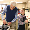 Brooklyn Smith, 12, looks over her shoulder at her teammate Jim Thrasher after he asks her how the cranberries he's cooking looks during the Chopped competition on Tuesday, Feb. 18, 2020. Western Middle School FACS club students and Waterford Place residents teamed up to prepare and cook a dish using certain ingredients in 45 minutes.<br /> Kelly Lafferty Gerber | Kokomo Tribune