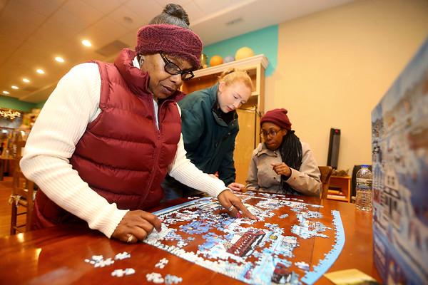 From left: Donita Humphries, Maddi Yockey, and Alyssa Newsome work on a puzzle together during Beyond Barcodes Bookstore's BlacKokomo History Fest on Friday, Feb. 7, 2020.<br /> Kelly Lafferty Gerber | Kokomo Tribune