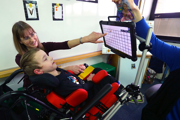 Haynes Elementary School l non-verbal students use touch screen devices to communitcate on January 31, 2020. Toryn Kaufman, who does not have accurate control of his arms, can stair at what he needs to say on the screen. Occupational Therapist Karen Scemaca helps guide him after he gets tired and distracted.<br /> Tim Bath | Kokomo Tribune