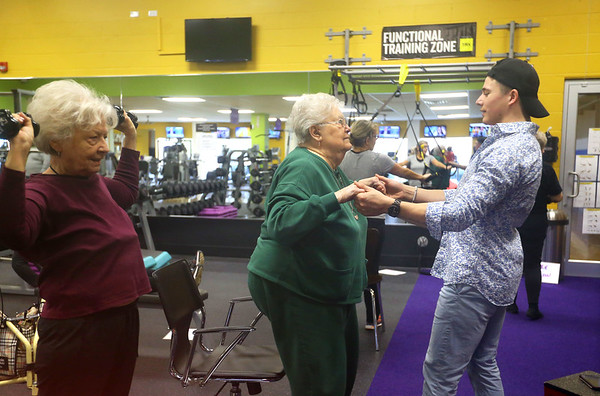 Dakota Cole helps Rita Goebel with exercises as Loue Lee lifts weights in the Actively Aging workout class at Tipton's Anytime Fitness on Jan. 22, 2020. Cole, manager of Tipton's Anytime Fitness, was on Undercover Boss when brand president of Anytime Fitness came for a visit.<br /> Kelly Lafferty Gerber | Kokomo Tribune