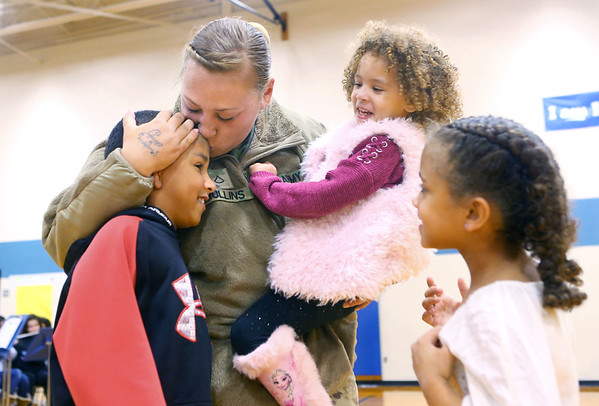 PFC Alicia Mullins kisses her 9-year-old son Zacariah Yarbrough and holds her 3-year-old daughter Zerrayah Mullins as her niece 7-year-old Jazzi Mullins waits for her hug after PFC surprised them at Bon Air Elementary after returning on Tuesday, January 14, 2020, from an 11-month deployment in Kuwait with the U.S. Army.<br /> Kelly Lafferty Gerber | Kokomo Tribune