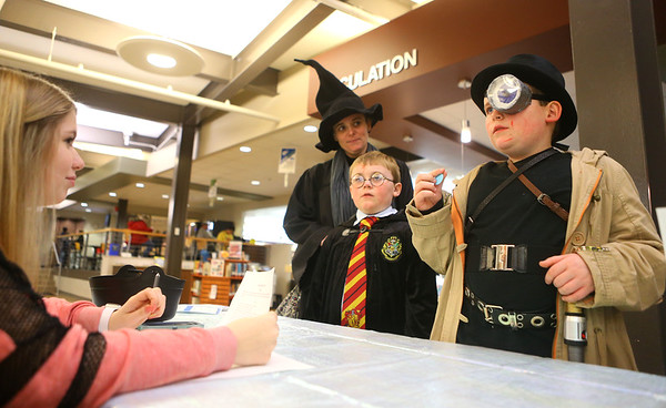 8-year-old Desmond Doss, right, dressed as Mad-Eye Moody, answers a trivia question alongside his brother Donovan Doss, 6, dressed like Harry Potter, and their mom Erin Doss, dressed like Professor McGonagall during the Harry Potter Yule Ball at Kokomo-Howard County Public Library on Friday, January 3, 2020.<br /> Kelly Lafferty Gerber | Kokomo Tribune