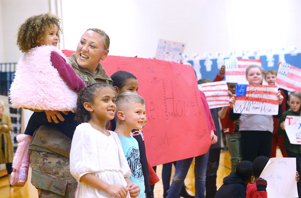 PFC Alicia Mullins holds her 3-year-old daughter Zerrayah Mullins as she poses for a photo with her 7-year-old niece Jazzi Mullins, 4-year-old nephew Jameson Tompkins, and 9-year-old Zacariah Yarbrough at Bon Air Elementary on January 14, 2020. PFC Mullins surprised them at school after returning from an 11-month deployment in Kuwait with the U.S. Army.<br /> Kelly Lafferty Gerber | Kokomo Tribune