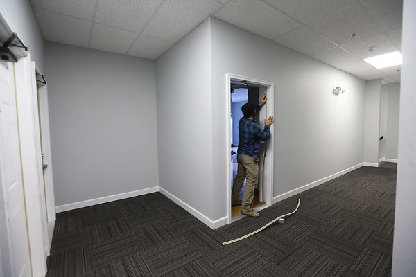 The College Apartments at the corner of Taylor and Main Streets on January 30, 2020. Fortune Management employee Kyle Chapman works on some finishing work, trim around a door.<br /> Tim Bath | Kokomo Tribune