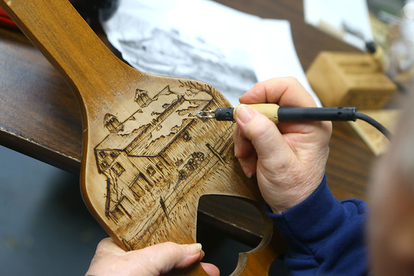 An Eastern Woodland Carver works on a wood burning piece on a longaberger paddle during an open carving meetin in Converse on January 14, 2020.<br /> Kelly Lafferty Gerber | Kokomo Tribune
