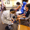 The Rescue Mission, in partnership with Crossroads Community Church and other area churches, helps income-qualified members of the community to come ÒshopÓ for free back to school shoes for students on Monday July 20, 2020. Krislyn Skiles helps Jasmin Hicks and her kids Lemont and Jamirri try on new pairs of shoes.<br /> Tim Bath | Kokomo Tribune