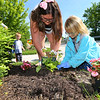 Lynlie Robinson 12, a cadet in Girl Scout Troop 560 and Brownie Amelia Kinney, 6, plant flowers along the Comet Trail at Harrison Street on Monday June 1, 2020.<br /> Tim Bath | Kokomo Tribune