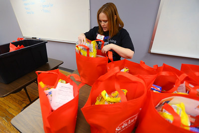 Voluteers from Community Howard, Solidarity FCU, and United Way fill buddy bags full of food on March 12, 2020. Libby O'Brien moves the food around so the bags can be packed in containers. Tim Bath | Kokomo Tribune