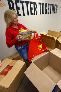 Voluteers from Community Howard, Solidarity FCU, and United Way fill buddy bags full of food on March 12, 2020. Diana Tenbrook loads a bag with food. Tim Bath | Kokomo Tribune