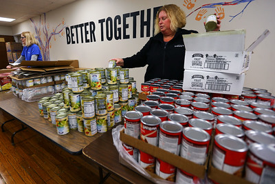 Voluteers from Community Howard, Solidarity FCU, and United Way fill buddy bags full of food on March 12, 2020. Sue Swales and Melissa Dominges stack food on tables that will be put in the bags. Tim Bath | Kokomo Tribune