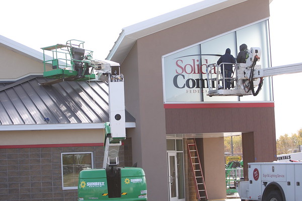 Martina Manns and Adam Elliott from Huston Signs puts the lettering on the windows of the new building of Solidarity FCU at Jefferson and Dixon Rd - Nov. 2, 2020.<br /> Tim Bath | Kokomo Tribune