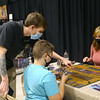 Demi card game creator Chaun Farmer, left, assists Frank Doughman as he learns how to play the game with  Emileigh Burker during Kokomo-Con.<br /> Kelly Lafferty Gerber | Kokomo Tribune