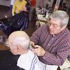 Barber Walt Moss cuts Clarence Robey's hair at Moss's shop on North Main Street on January 11, 2001.<br /> File photo
