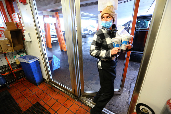 Kamy Watson takes an order of food and drinks to a car at Barker's B & K at 1100 East Markland on season opening day  on Tuesday Jan. 26, 2021.<br /> Tim Bath | Kokomo Tribune