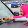 "Third grader Libby Anderson ""ducks"" a Jeep in the Meijer parking lot on Tuesday, January 19, 2021."