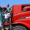 Kyle Musselman and his son Kasen, 4, prepare to climb down off the combine on Thursday, July 1, 2021.<br /> Kelly Lafferty Gerber | Kokomo Tribune
