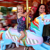 7-14-21<br /> Three year-old Naomi Riggs rides the carousel with her mom at the Howard County Fair Wednesday.<br /> Tim Bath | Kokomo Tribune