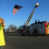 Malachi Fronczak salutes as Fire Engine 6, carrying the casket of Captain Marty Meyers, passes under the garrison flag at Fire Station 6 on Tuesday, March 9, 2021.<br /> Kelly Lafferty Gerber | Kokomo Tribune
