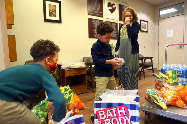6-year-old Jaylin Frazier, center, with help from his 8-year-old cousin Kameron Jefferson, left, and their grandmother Robin Miller, right, delivered a food and monetary donation, as well as gifts for staff and volunteers at the Kokomo Rescue Mission on Wednesday, March 10, 2021.<br /> Kelly Lafferty Gerber | Kokomo Tribune