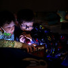 """Second grade 8-year-old's Cooper Creason, left, and Kyler Shear use a flashlight as they take turn reading to each other as they, along with other Redeemer Lutheran students, have a """"sleepout experience"""" in their gym on Friday, March 12, 2021, to raise awareness of homelessness.<br /> Kelly Lafferty Gerber 