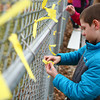 4-2-14<br /> Ryan Beining memorial service<br /> 8-year-old Kayden Pax ties a yellow ribbon on the fence outside Ryan's Field, a baseball field at Taylor Intermediate named after Ryan Beining.<br /> KT photo | Kelly Lafferty