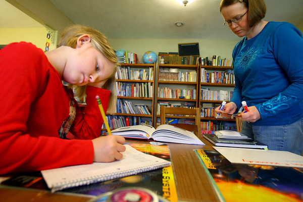 3-18-14   --- Jennifer Mayfield with her kids Katie, 9, and Anna, 11, during home school time. Katie takes a spelling test with mom preparing the next lesson. -- <br />   Tim Bath | Kokomo Tribune