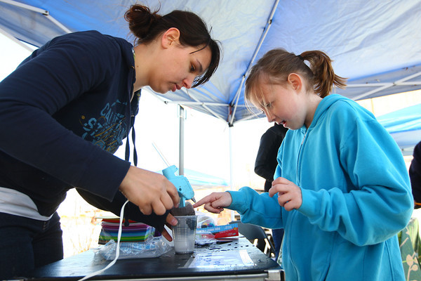 4-19-14<br /> Farmers Market<br /> Rachelle Spence (left) helps Sydney Lechner, 9, make a craft in the Little Sprouts' Market Club at the opening day of Kokomo's Farmers' Market.<br /> Kelly Lafferty | Kokomo Tribune