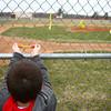 4-2-14<br /> Ryan Beining memorial service<br /> 9-year-old Logan Sinnett ties a yellow ribbon on the fence surrounding Taylor Intermediate's baseball diamond, called Ryan's Field.<br /> KT photo | Kelly Lafferty