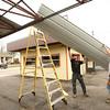 4-10-14<br /> Rebuilding Peru's BK<br /> J.D. Mock and Justin Graber manuever a piece of aluminum siding onto the roof of Peru's BK as they rebuild it.<br /> Kelly Lafferty | Kokomo Tribune